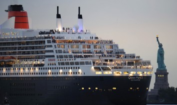 The Queen Mary 2 sails  near the Statue of Liberty in New York Harbor to meet the QE2 in New York.